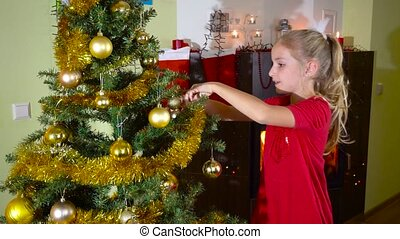 cute girl decorating christmas tree near the fireplace