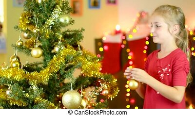 cute girl decorating christmas tree near the fireplace. Slow...