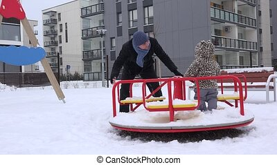 Happy family man with girl spin on circle swing in winter playground. 4K