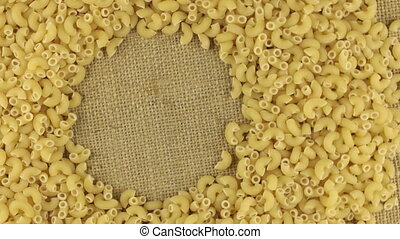 Rotation of the pasta lying on sackcloth with space for your text