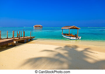 Boat and bungalow on Maldives island - nature travel...