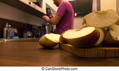 Man using juicer in the kitchen. Making apple juice at home....