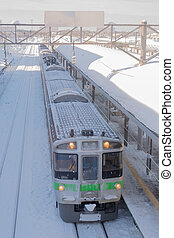 Train stop at railway station with snow of winter in Japan.