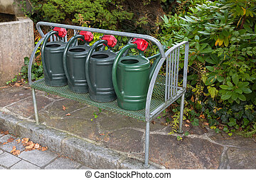 Green plastic watering cans with coin lock on metal shelf near the cemetery