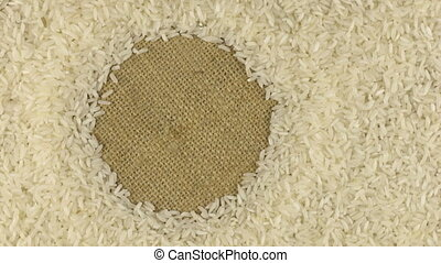 Rotation of the rice grains lying on sackcloth with space for your text
