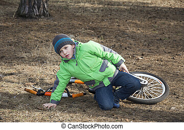Spring in the forest boy fell off his bicycle.