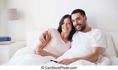 happy couple watching tv in bed at home - people, leisure,...