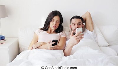 happy couple with smartphones in bed