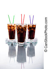 three glasses of cola with ice and straws on a white...