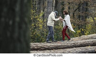Senior couple in autumn forest walking on wooden logs -...