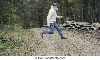 Senior man in colorful autumn nature posing and jumping -...