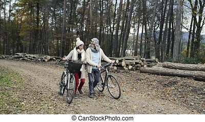 Senior couple with bicycles walking in autumn nature -...