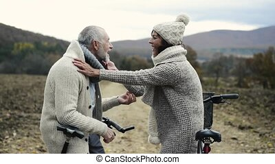Senior couple with bicycles resting in autumn nature -...