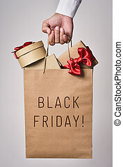 shopping bag full of gifts and text black friday - closeup...