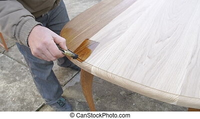 Carpenter is covering table by lacquer - Carpenter is...