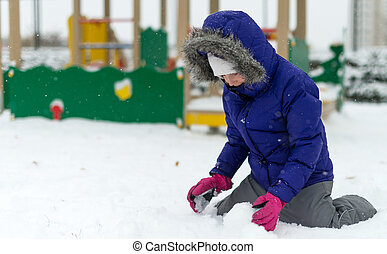 Little girl rolling snowball in winter.