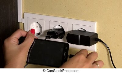 woman hand attach smart phone to wall charger and hold in...