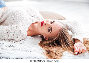 Attractive woman in sweater lying on the carpet at home