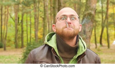 A bearded man in a sweater and leather jacket in the fall...