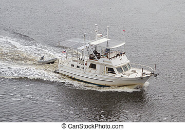 An Older White Boat - An Older Boat Cruising Down the...