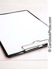 Clipboard on the wooden background