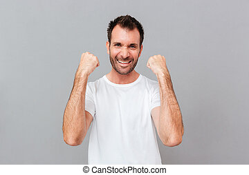 Happy excited young casual man celebrating success over grey...