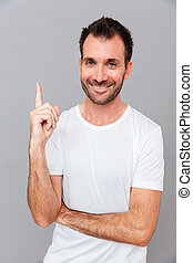 Handsome smiling man having an idea and pointing finger up