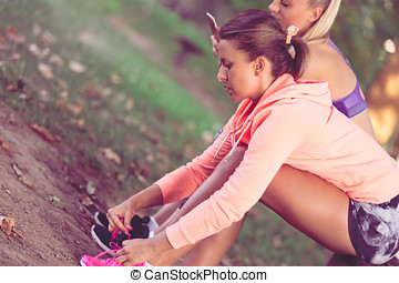 Young sportive woman getting ready to start running workout...