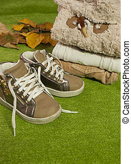 Happy feet - Brown children sneakers on the green background