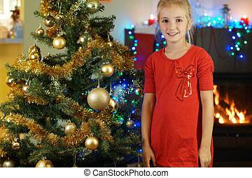 cute girl in red dress near Christmas tree