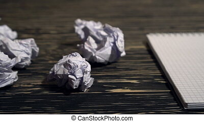Person throwing a lot of crumpled paper on a desk, close-up.