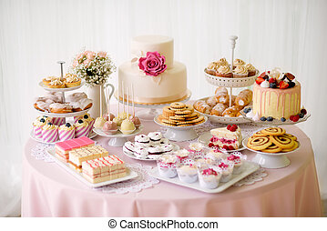 Table with loads of cakes, cupcakes, cookies and cakepops....
