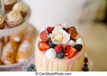 Cake with various berries and meringues on a stand. Cupcakes...