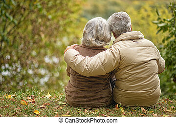 Elderly couple sitting with his back embracing in autumn...