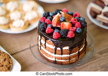 Naked cake with chocolate and berries, cookies and tarts -...