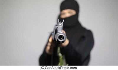 Woman with a machine gun. Muslim woman pointing a machine...