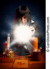 Fortuneteller - Gothic girl with a crystal ball and candles...