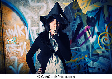 Pretty witch posing over wall with graffiti