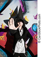Stop! - Pretty young witch in hat posing over wall with...