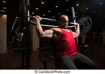 Muscular Man Doing Heavy Weight Exercise For Shoulders -...
