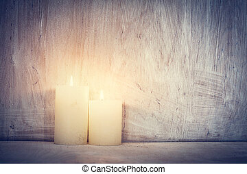 Chistmas candle glowing on rustic wooden wall background.....