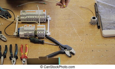 Man hands twist off white wires from circuit breaker with...