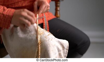 View of craftsman cleans twig from bark - Basketry. View of...