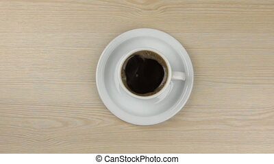 Approximation of hot steaming cup of coffee standing on a wooden table