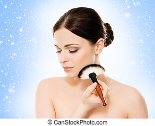 Face of a healthy woman holding a makeup brush - Face of...