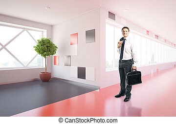 Businessman in modern corridor - Side view of smiling young...