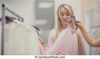 The blonde with long hair in a pink dress shopping with a...