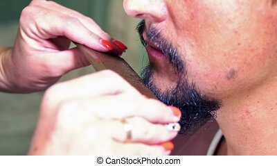 Man combs his beard - Female hand are combing beard and...