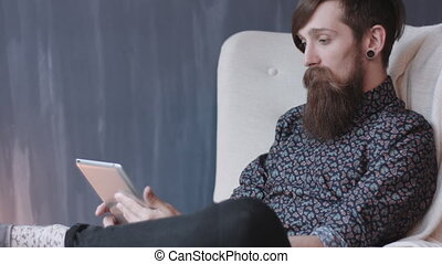 Hipster using digital tablet. - Hipster with beard and...