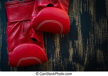 Red leather boxing gloves on a black background